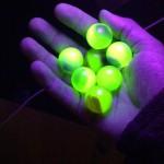 mão segurando bolitas que contém urânio