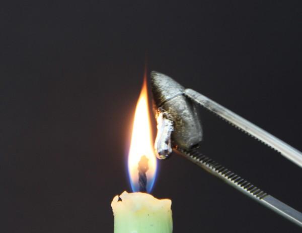 pinça segurando chumbada sobre chamde de vela