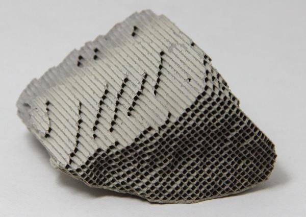 pedaço irregular de um catalisador usado em escapamento