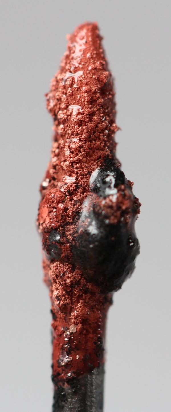 ponta de um grafite com metal de cobre de cor avermelhada